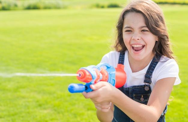 Smileymädchen, das mit wasserwerfer spielt Kostenlose Fotos