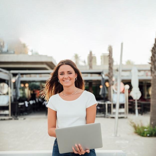 Smileymädchen mit dem notizbuch, das kamera betrachtet Kostenlose Fotos