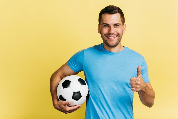 Smileymann, der eine fußballkugel anhält Kostenlose Fotos