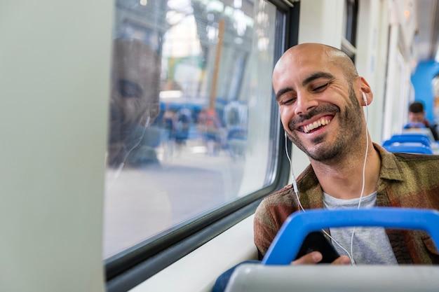 Smileyreisender mit kopfhörern in der metro Kostenlose Fotos