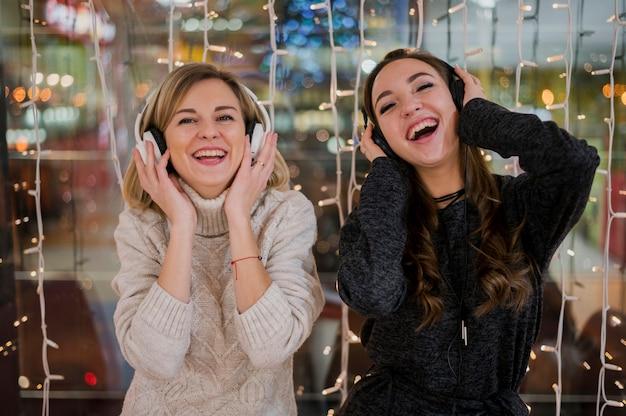 Smilig frauen, die kopfhörer nahe weihnachtslichtern tragen Kostenlose Fotos