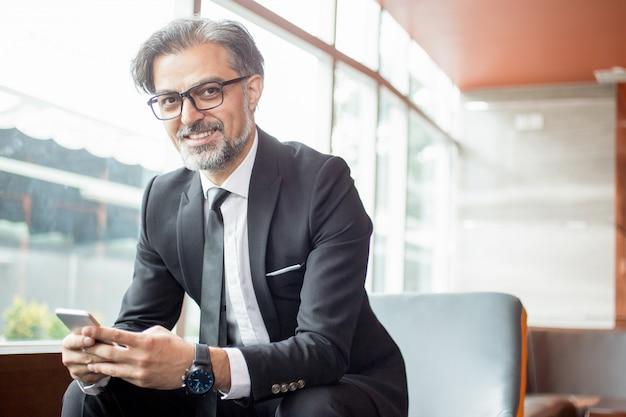 Smiling business leader mit smartphone in der lobby Kostenlose Fotos
