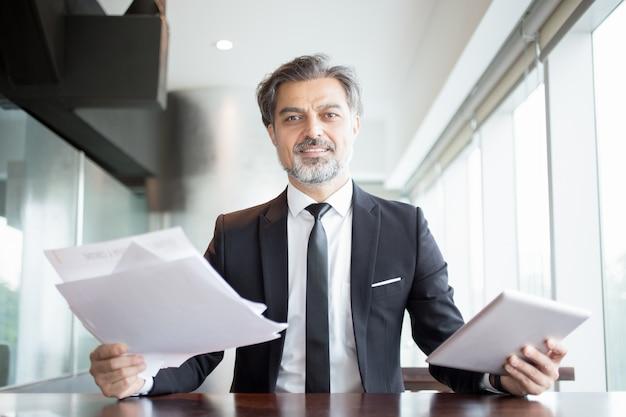 Smiling business man holding tablet und dokumente Kostenlose Fotos