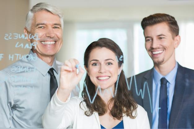 Smiling business team zeichnung diagramm auf glasschirm Kostenlose Fotos