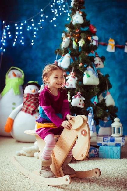 smiling kleines m dchen in der n he der weihnachtsbaum. Black Bedroom Furniture Sets. Home Design Ideas
