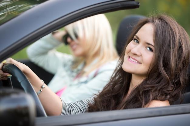 Smiling mädchen ein cabrio auto fahren Premium Fotos