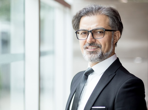 Smiling middle-aged business leader am fenster Kostenlose Fotos