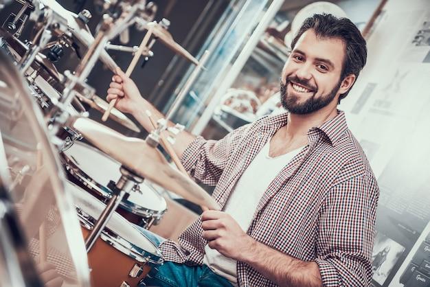 Smilling bärtiger mann im hemd spielt auf schlagzeug. Premium Fotos