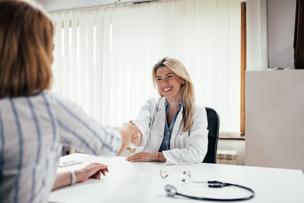 Smling ärztinhändedruck mit einem patienten. Premium Fotos