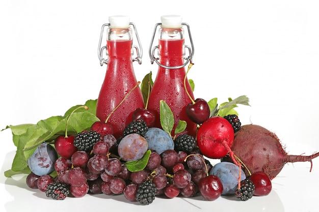 Smoothies. burgunder-smoothies in den glasflaschen lokalisiert auf weiß. Premium Fotos