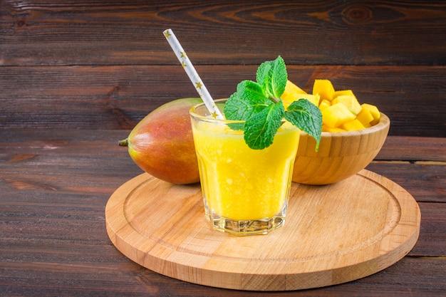 Smoothies mango mit stroh und minze in einem becherglas. platte mit geschnittener mango. Premium Fotos