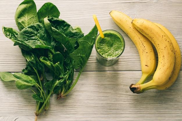 Smoothies mit einem strohhalm, einer banane und spinat verlässt auf weißem hölzernem hintergrund Premium Fotos
