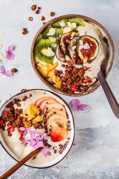 Smoothieschüssel mit frucht und granola mit kokosschalenschüssel auf grauem hintergrund. gesundes veganes essen. Premium Fotos