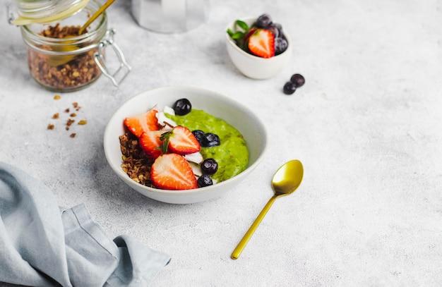 Smothie-schüssel mit avocado, banane, spinat, kokosmilch mit müsli, blaubeeren, erdbeeren und kokosnusschips. gesundes frühstückskonzept. nahrung zur stärkung der immunität. draufsicht mit copyspace Premium Fotos