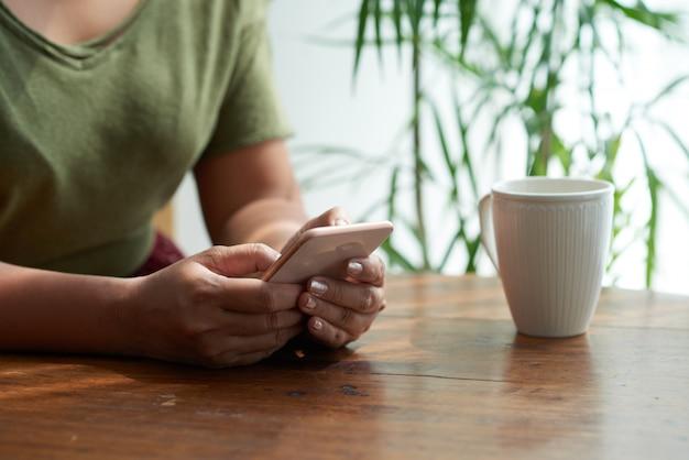 Sms mit freund im gemütlichen café Kostenlose Fotos