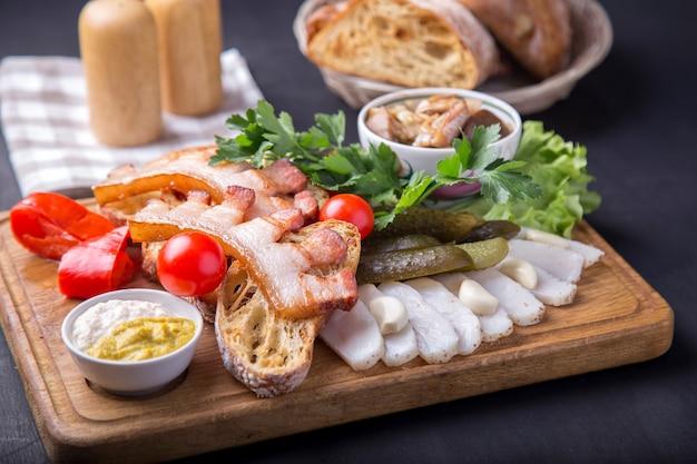 Snack mit gebratenem bruststück, brot, geschnittenem schmalz, frischen tomaten und marinierten pilzen. leckere vorspeise auf holzbrett Premium Fotos