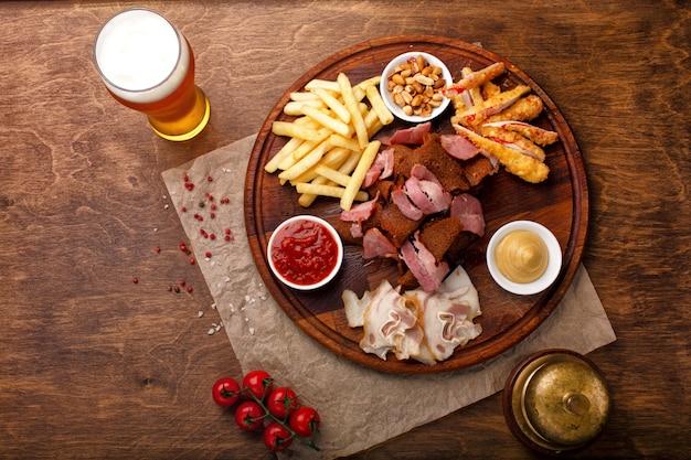 Snacks für bier oder alkohol. dazu gehören geräuchertes schweinefleisch, pommes frites, gebratenes brot, krabbenstäbchen und nüsse Premium Fotos