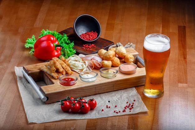 Snacks für bier umfasst gebratene käsebällchen, zopfkäse, schinken und krabbenstäbchen auf einem holzbrett Premium Fotos