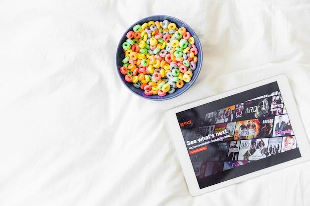 Snacks in der Nähe von Tablet mit Netflix-Website Kostenlose Fotos