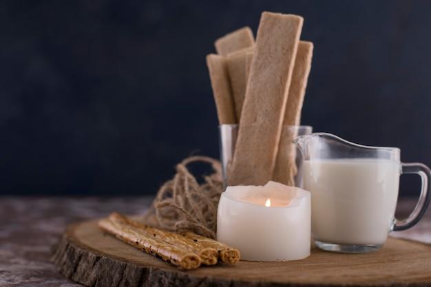 Snacks und cracker mit einem glas milch auf einem holzbrett. Kostenlose Fotos