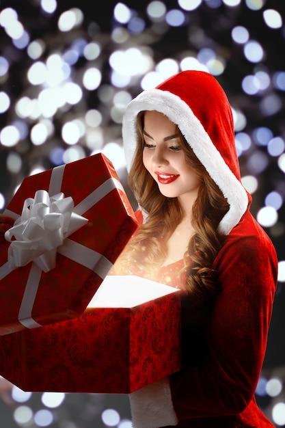 Snow maiden im roten anzug eröffnet ein rotes geschenk für weihnachten und neujahr 2018,2019 Kostenlose Fotos