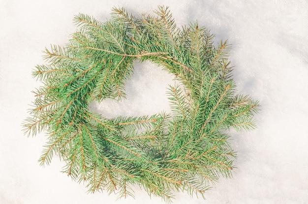 Snowy bereifter weihnachtskranz. kranz aus tannenzweigen auf schnee. Premium Fotos