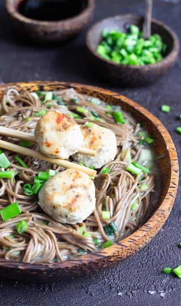 Soba-nudeln, serviert mit hühnerfleischbällchen und frühlingszwiebeln. Premium Fotos