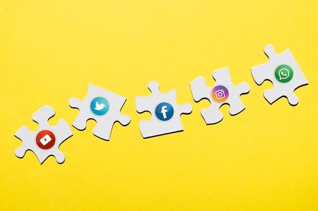 Social media-ikone auf weißem puzzlespielstück über gelbem hintergrund Kostenlose Fotos