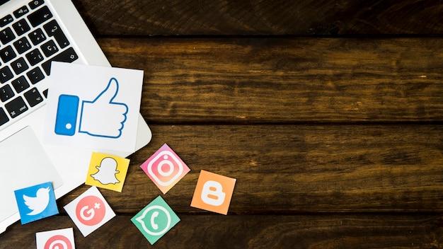 Social media-ikonen mit ähnlicher ikone auf laptop über hölzernem hintergrund Kostenlose Fotos