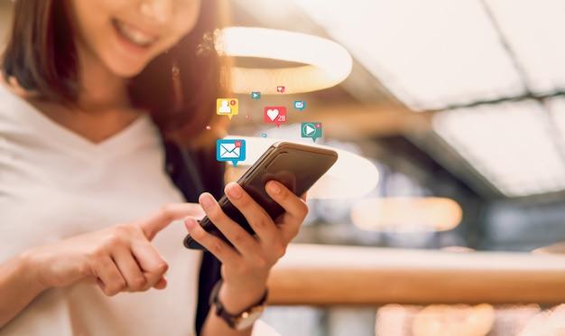 Social media und digitales online, lächelnde asiatin, die smartphone- und showtechnologieikone verwendet. Premium Fotos