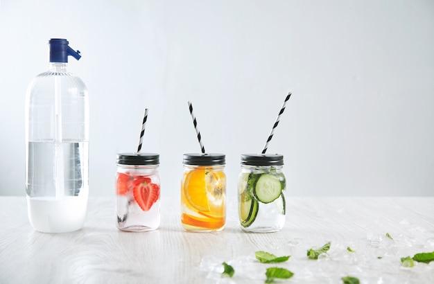 Soda siphon flasche in der nähe von drei rustikalen gläsern mit eisigen frischen getränken aus erdbeere, orange, limette, minze, gurke und mineralwasser Kostenlose Fotos