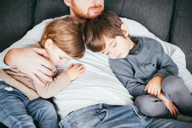Söhne, die auf der brust ihres vaters schlafen Kostenlose Fotos