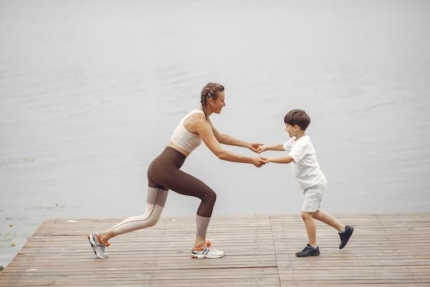 Sohn und mutter machen übungen im sommerpark. familie am wasser. Kostenlose Fotos
