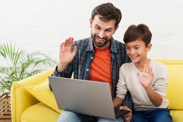 Sohn und vater, die einen laptop und eine begrüßung halten Kostenlose Fotos