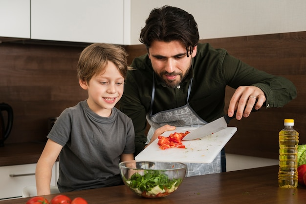 Sohn und vater, die zu hause salat kochen Kostenlose Fotos