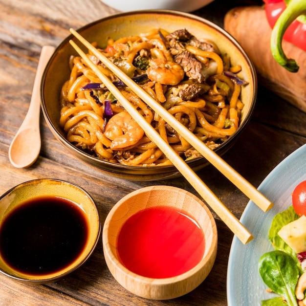 Soja- und rote chili-saucenschüssel mit udon-nudeln und essstäbchen über dem tisch Kostenlose Fotos