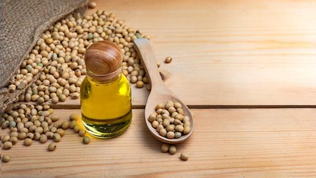 Soja- und sojaöl befinden sich in einem sack. auf einen holztisch gelegt Premium Fotos