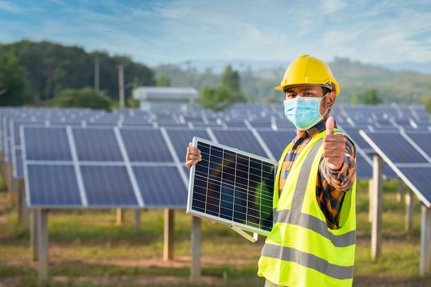 Solarenergietechniker stehend, solarzellen haltend und daumen hoch, solarzellenpanel mit starker sonne. Premium Fotos