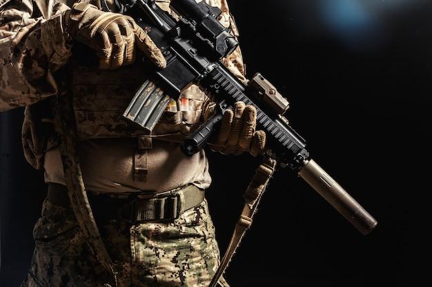 Soldat der besonderen kräfte mit gewehr auf dunkelheit Premium Fotos