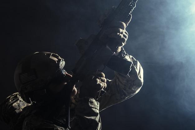 Soldat der besonderen kräfte mit gewehr auf dunklem hintergrund Premium Fotos