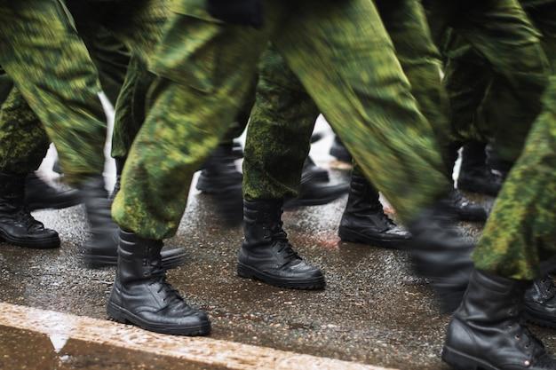 Soldatenstiefel, die auf nassen asphalt während der parade des gedächtnisses gehen. das militär marschiert die straße entlang. viele schuhe und tarnkleidung. bewegungsschmierung Premium Fotos
