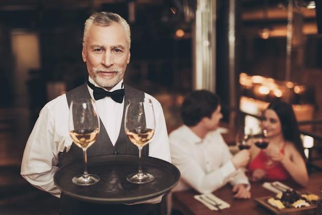 Sommelier hält tablett mit gläsern weißwein. Premium Fotos