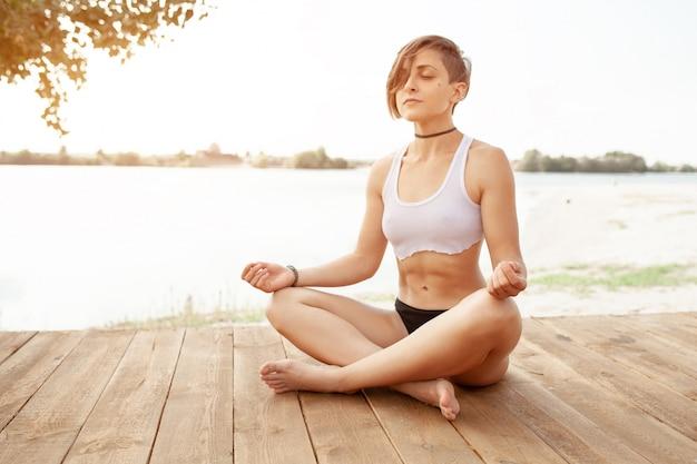 Sommer. ein schönes mädchen mit kurzem haarschnitt praktiziert yoga Premium Fotos