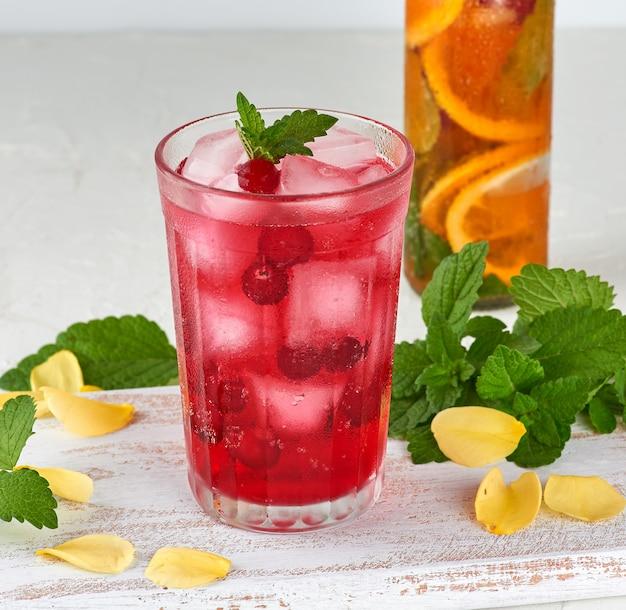 Sommer-erfrischungsgetränk mit preiselbeeren und eisstücken in einem glas Premium Fotos