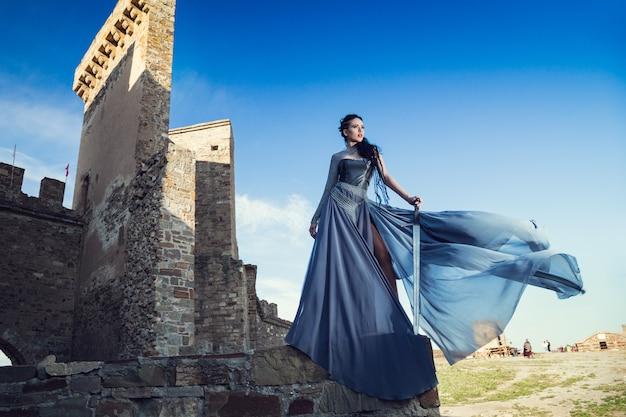 Sommer im freien porträt der schönen wütenden skandinavischen krieger ingwerfrau im grauen kleid mit metallkettenhemd. Premium Fotos