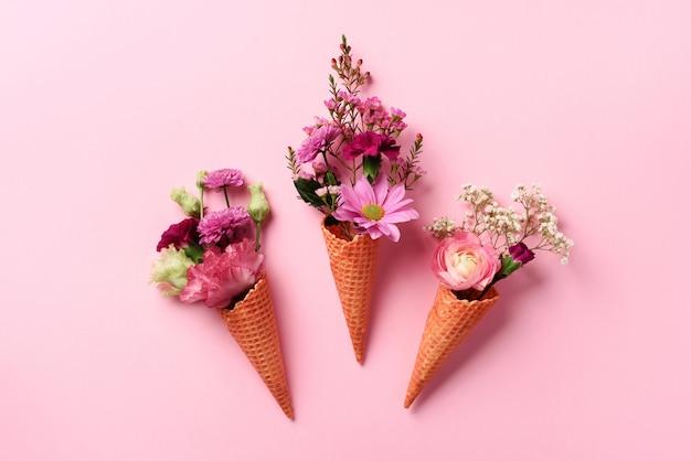 Sommer minimales konzept. eistüte mit rosa blumen und blättern auf schlagkräftigem pastellhintergrund. Premium Fotos