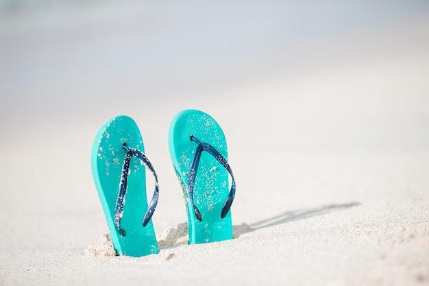 Sommer minze flip flops mit sonnenbrille am weißen strand Premium Fotos