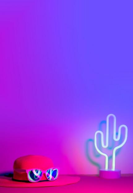 Sommer mit hut und sonnenbrille refection neonlicht mit kaktus auf rosa und blauem licht auf tabelle Premium Fotos