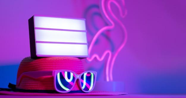 Sommer mit leerem ligh kasten auf hut mit sonnenbrille refection flamingoneonrosa und blau auf tabelle Premium Fotos