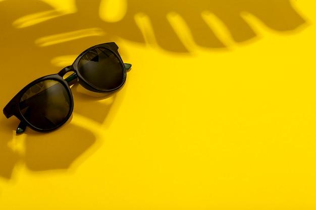 Sommer- und urlaubskonzept. sonnenbrillen im schatten tropischer wahrheiten und pflanzen auf einem hellen sauberen sommerhintergrund Premium Fotos